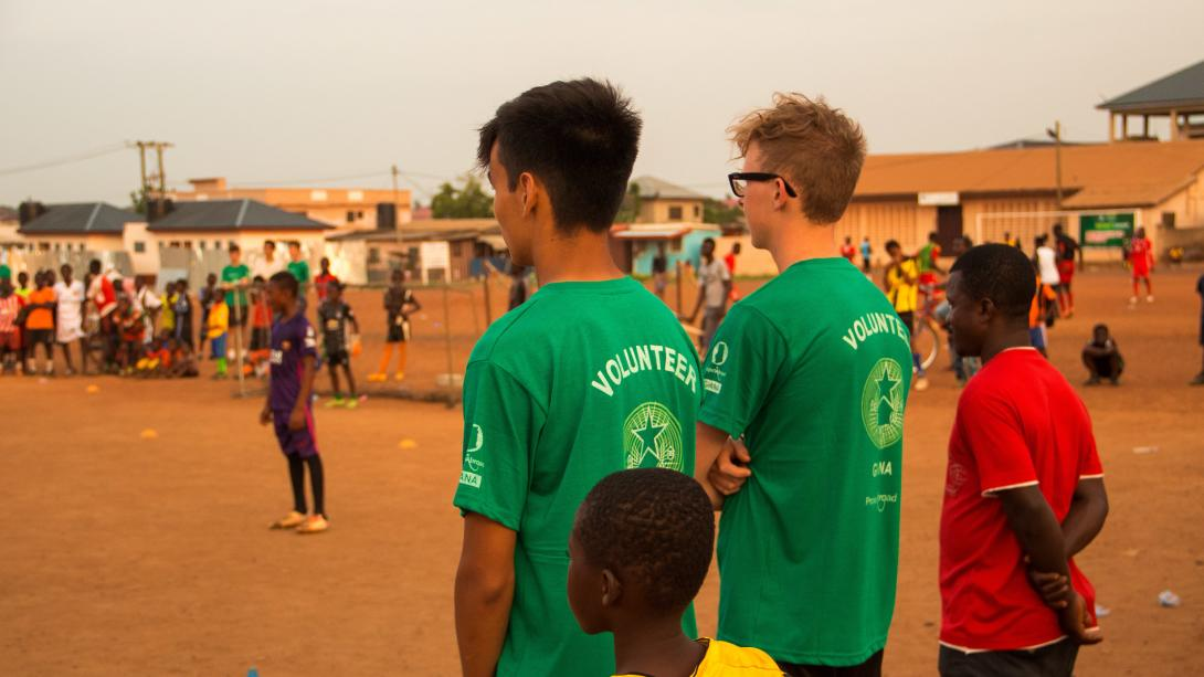 Sports coaches watch their students play a game of football after practice in Ghana.